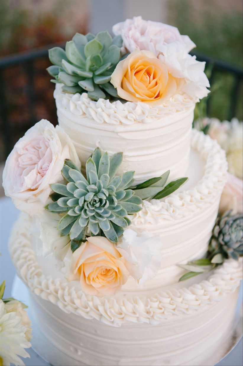 buttercream wedding cake decorated with roses and succulents