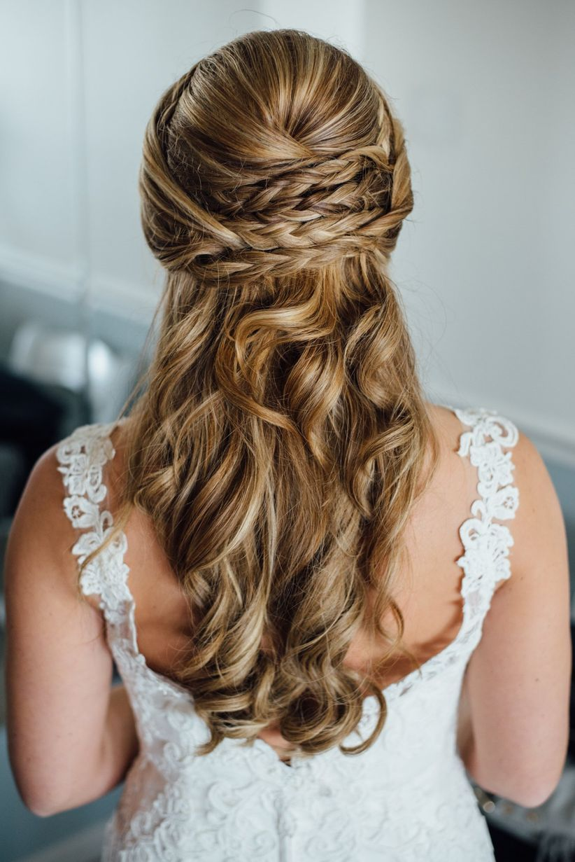 bride with curly half up hairstyle and braids