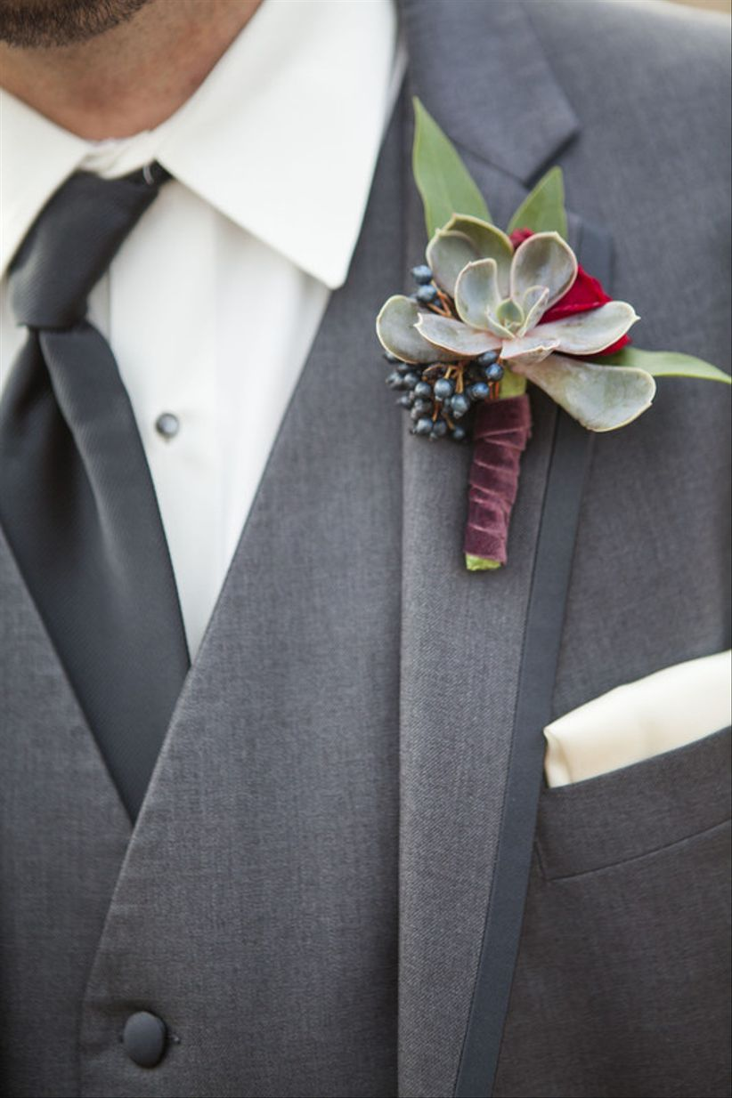 Succulent boutonniere with dark blue berries and purple velvet ribbon