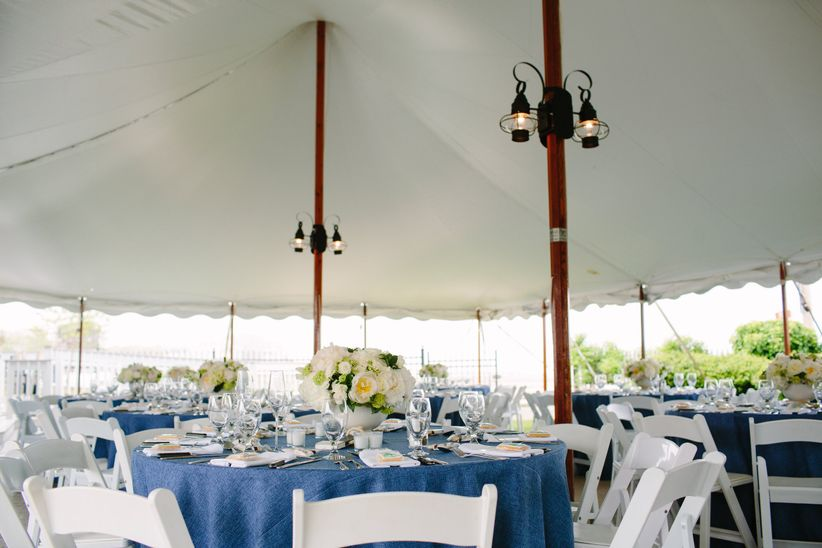 Blue tables and white chairs under a tent outside