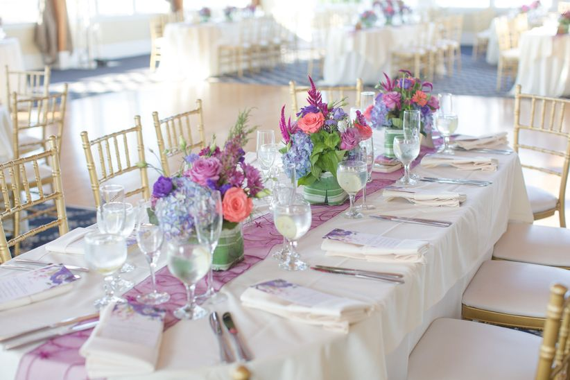 wedding reception table with purple and pink centerpieces