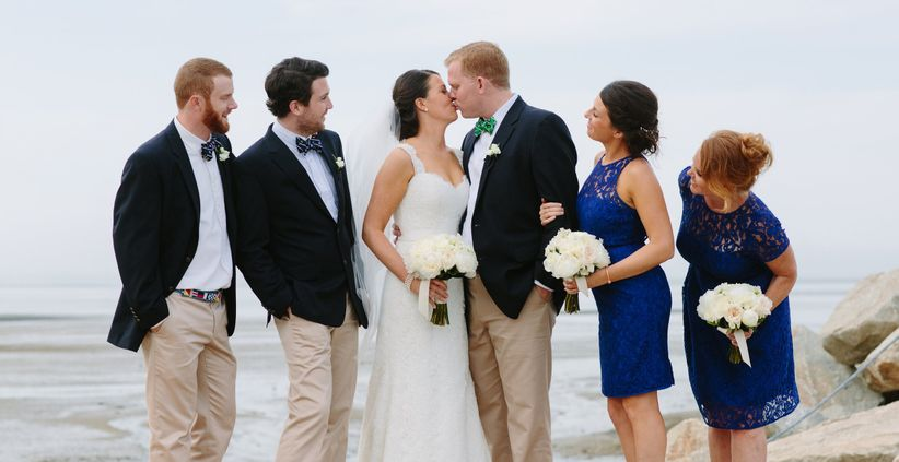 Two groomsmen, two bridesmaids, watch the ceremony kiss on a beach
