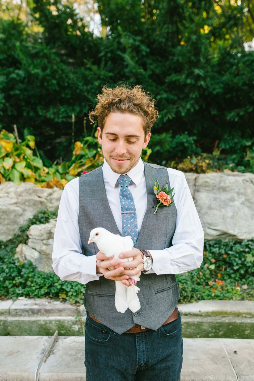 groom holding dove