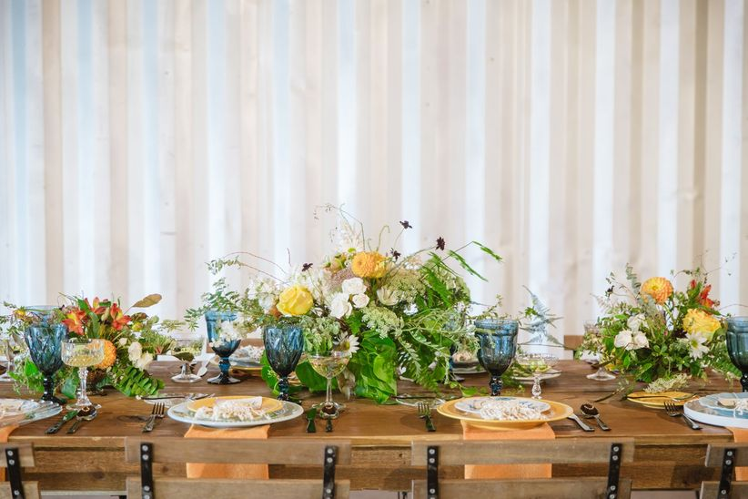 bohemian summer wedding tablescape with greenery centerpiece and yellow decor
