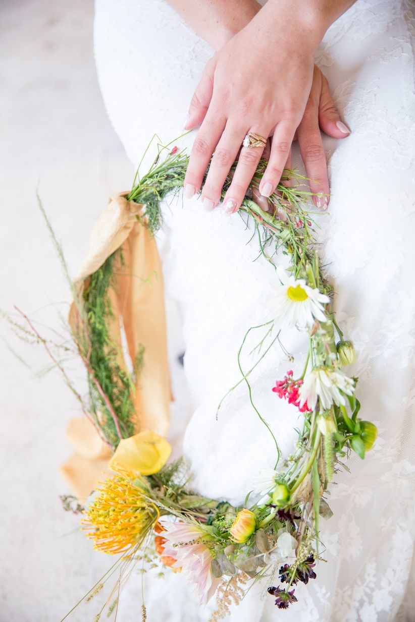bride carrying bohemian wedding wreath with greenery and daisies