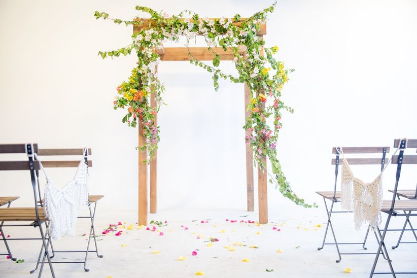 indoor bohemian wedding altar with flowers and greenery