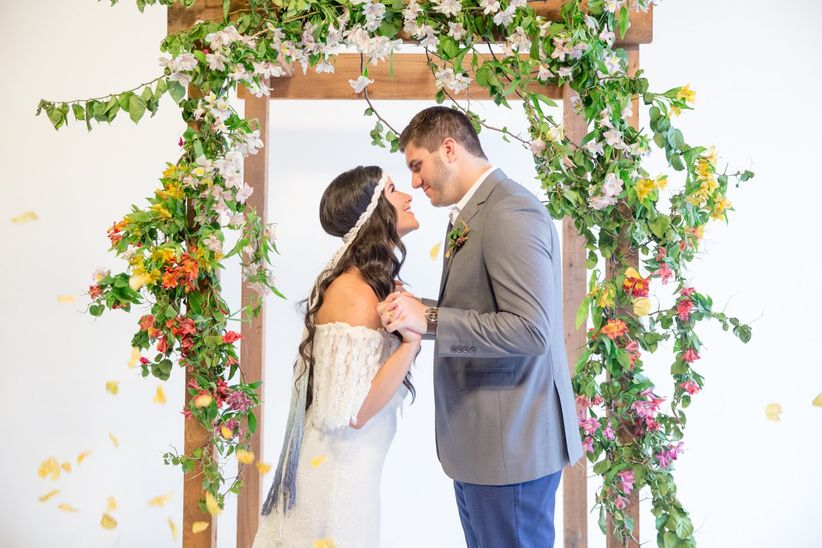boho bride and groom at indoor wedding with floral ceremony backdrop