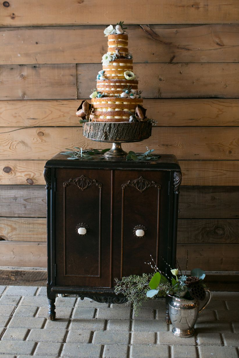rustic naked wedding cake adorned with flowers wooden slice display