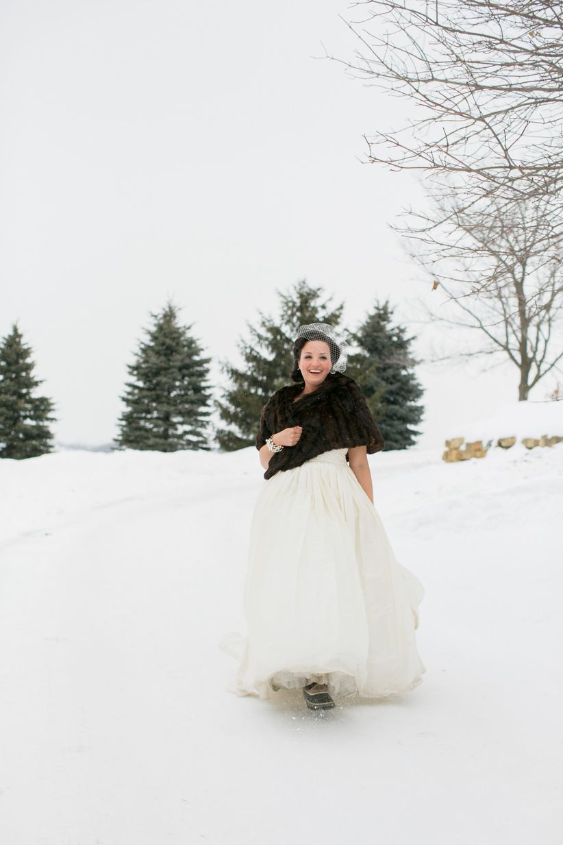 bride walking in snow taffeta ball gown brown fur stole