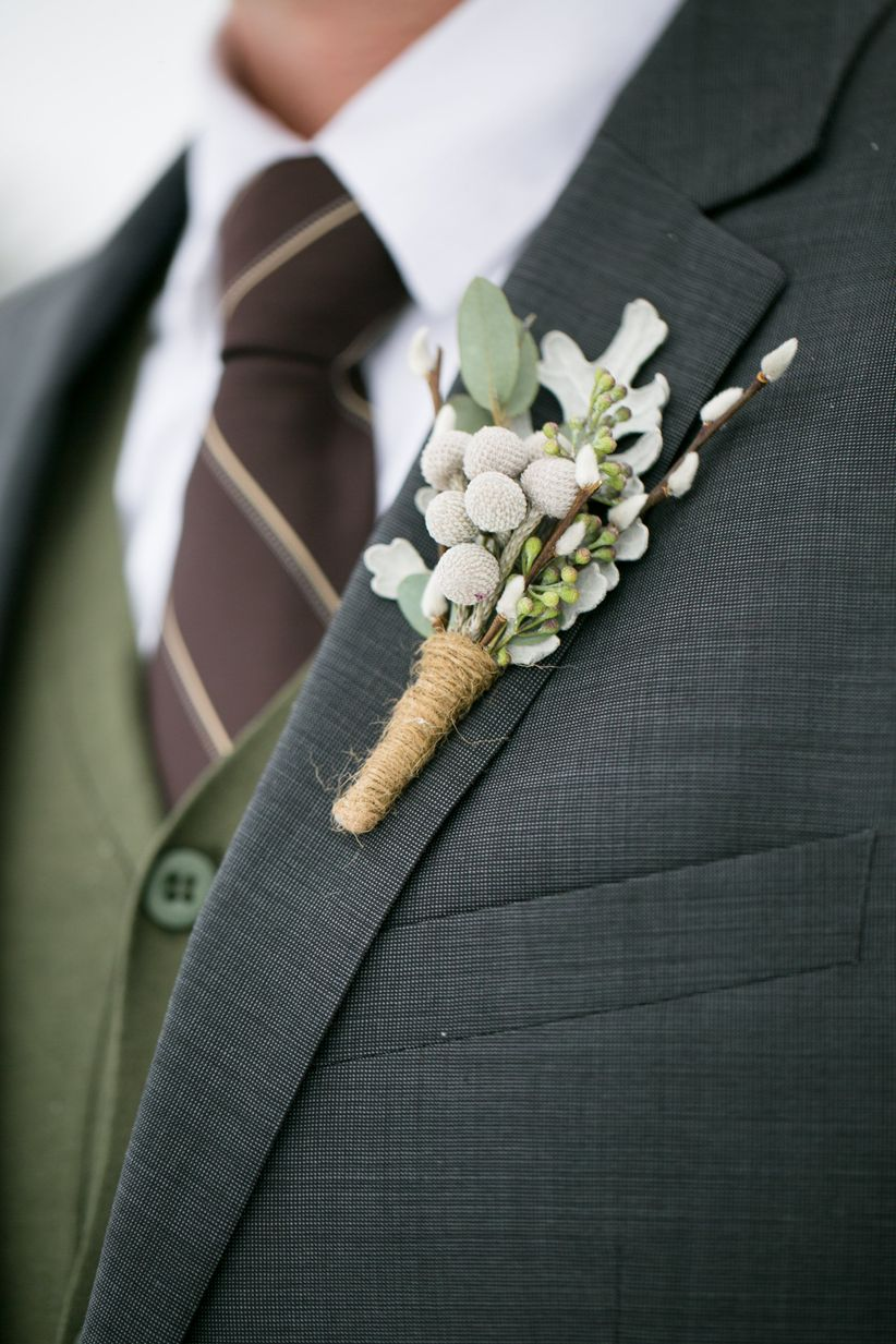 close up groom's attire charcoal gray suit paired with a forest green vest, and brown striped necktie