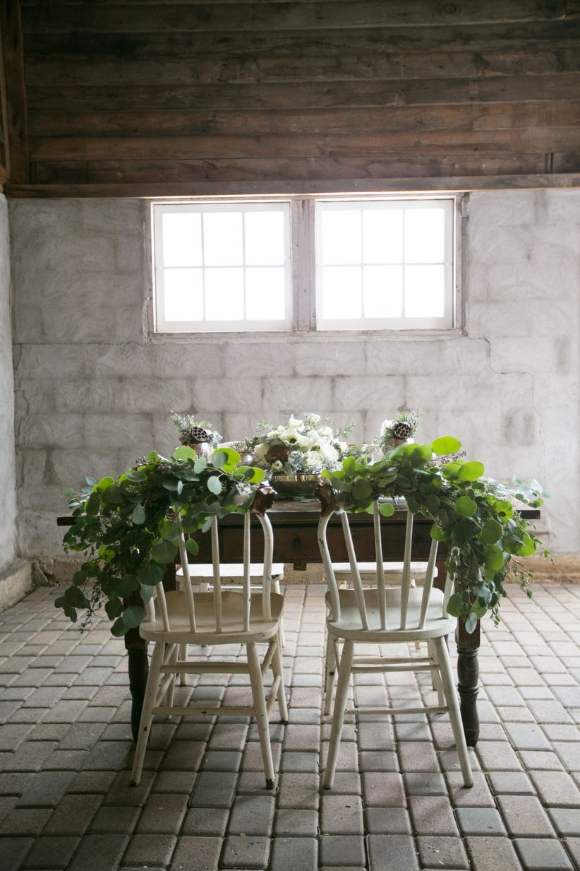 rustic vintage-inspired simple tablescape white chairs adorned with greenery