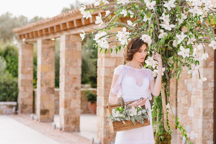 bride in chiffon gown posed next to blooming tree with basket of flowers