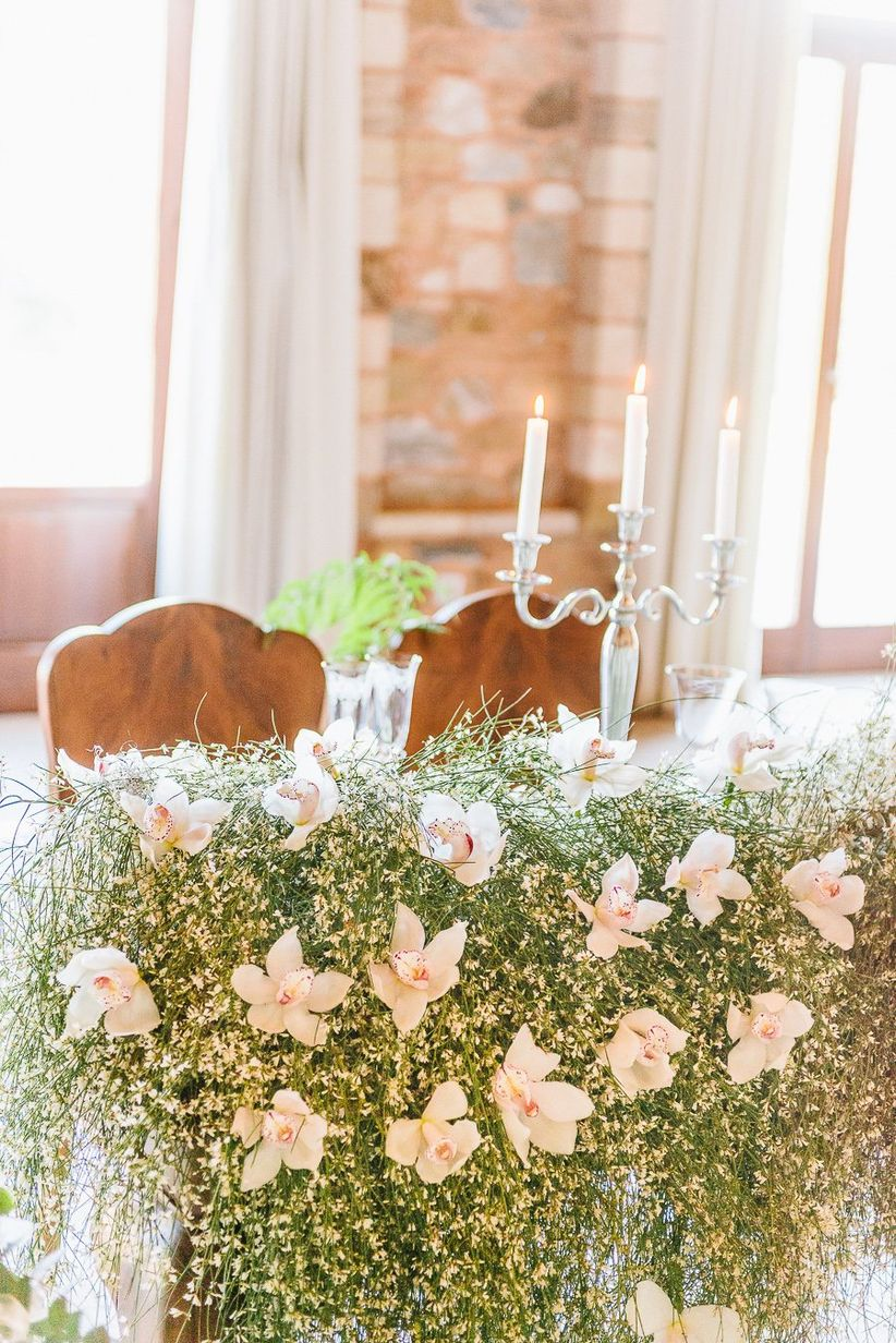 sweetheart table covered with cascading floral centerpiece