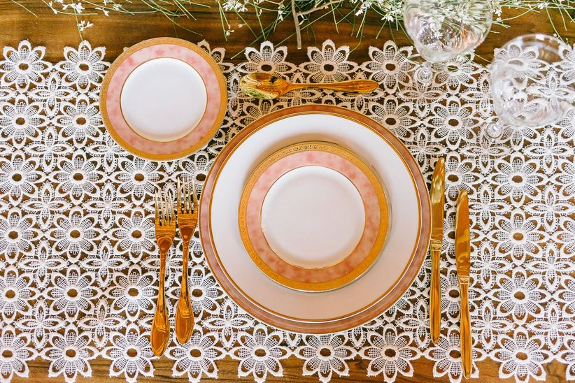 close up place setting pink gold and white plates and cutlery