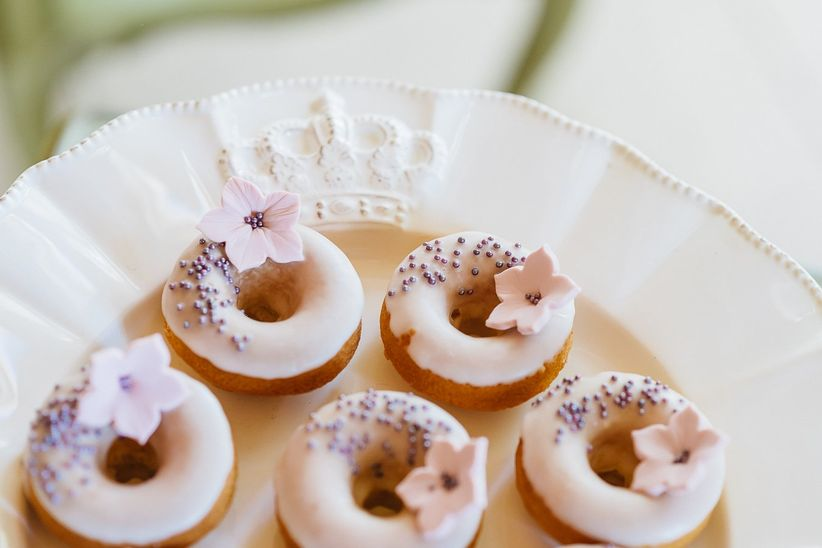 mini glazed doughnuts with purple sprinkles and pink lily sugar flowers