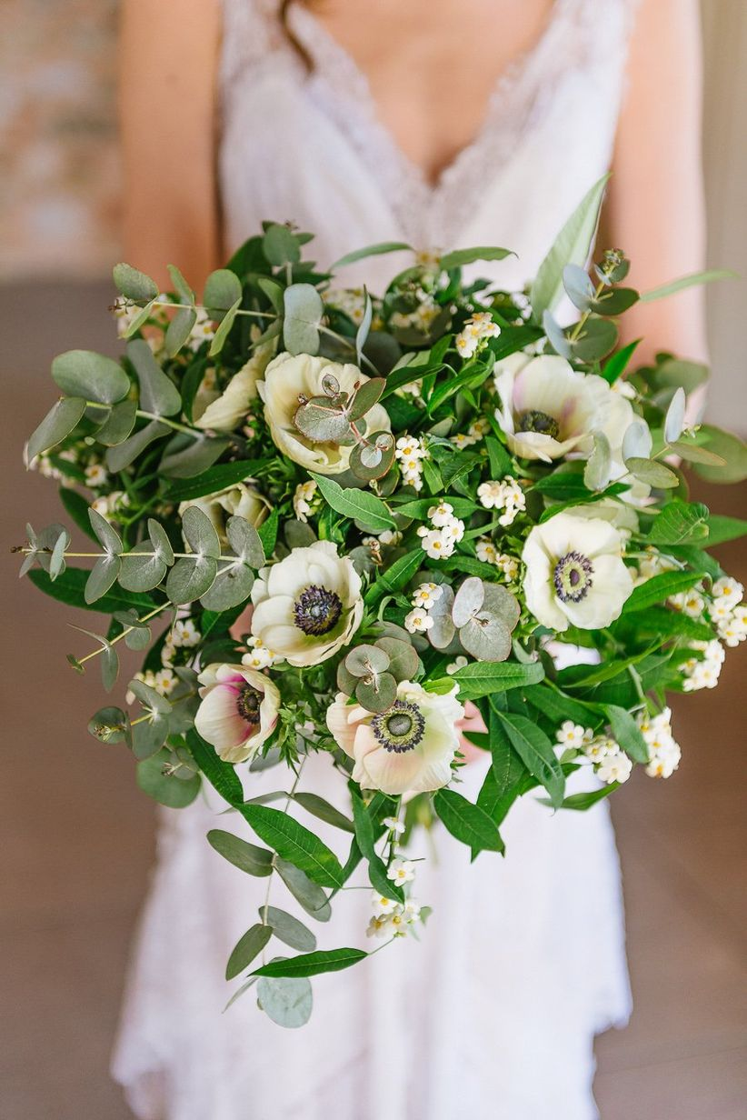 bride holding bouquet featuring anemones, waxflower, ruscus, and eucalyptus