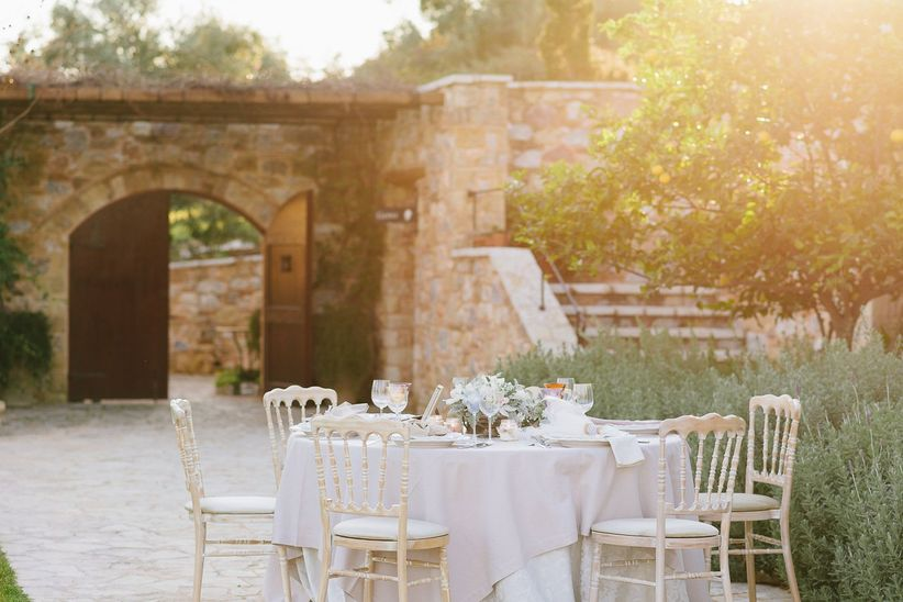 elegant outdoor tablescape white and blush linens gold versailles chairs