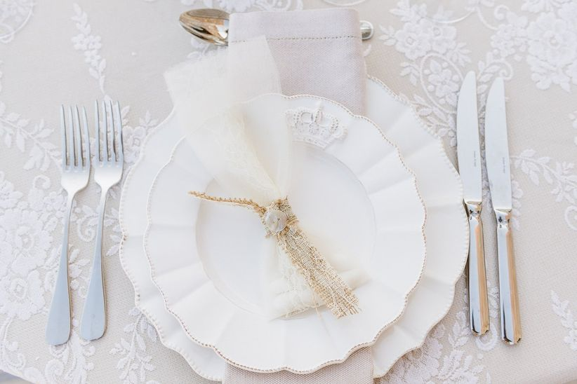 close up place setting white scalloped plates favor pouch lace and burlap
