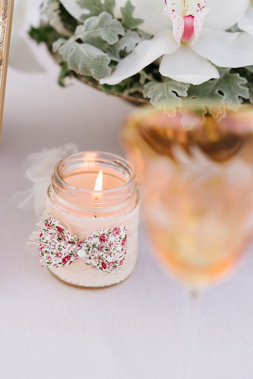 close up votive candle wrapped in lace and attached with small floral bow