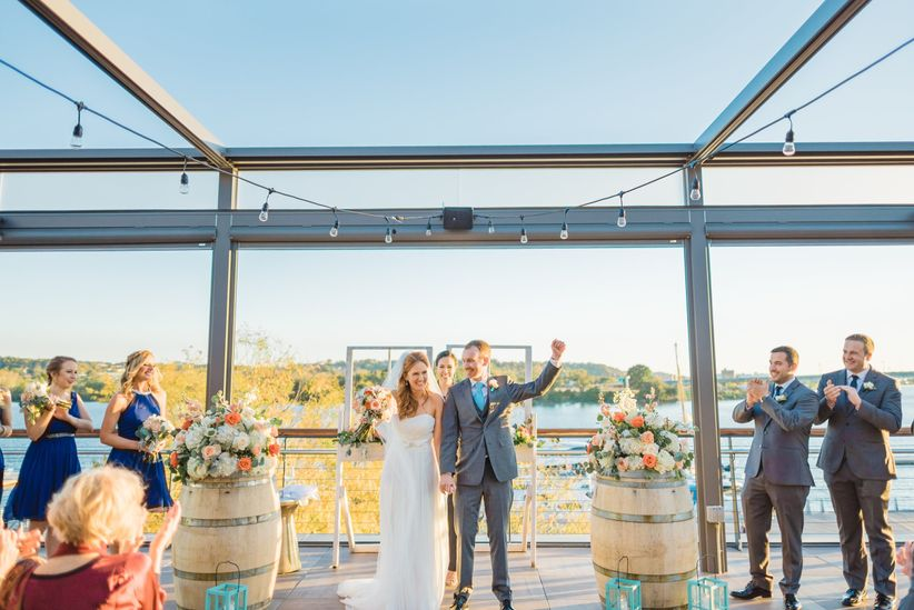 bride and groom hold hands and face their guests after their wedding at district winery
