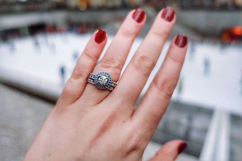 round engagement ring with blue sapphire halo and matching wedding band