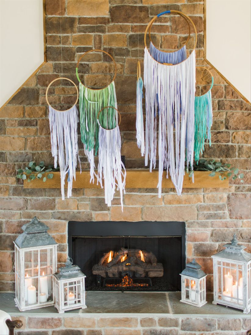 stone fireplace decorated with boho fringe hoops at indoor wedding venue