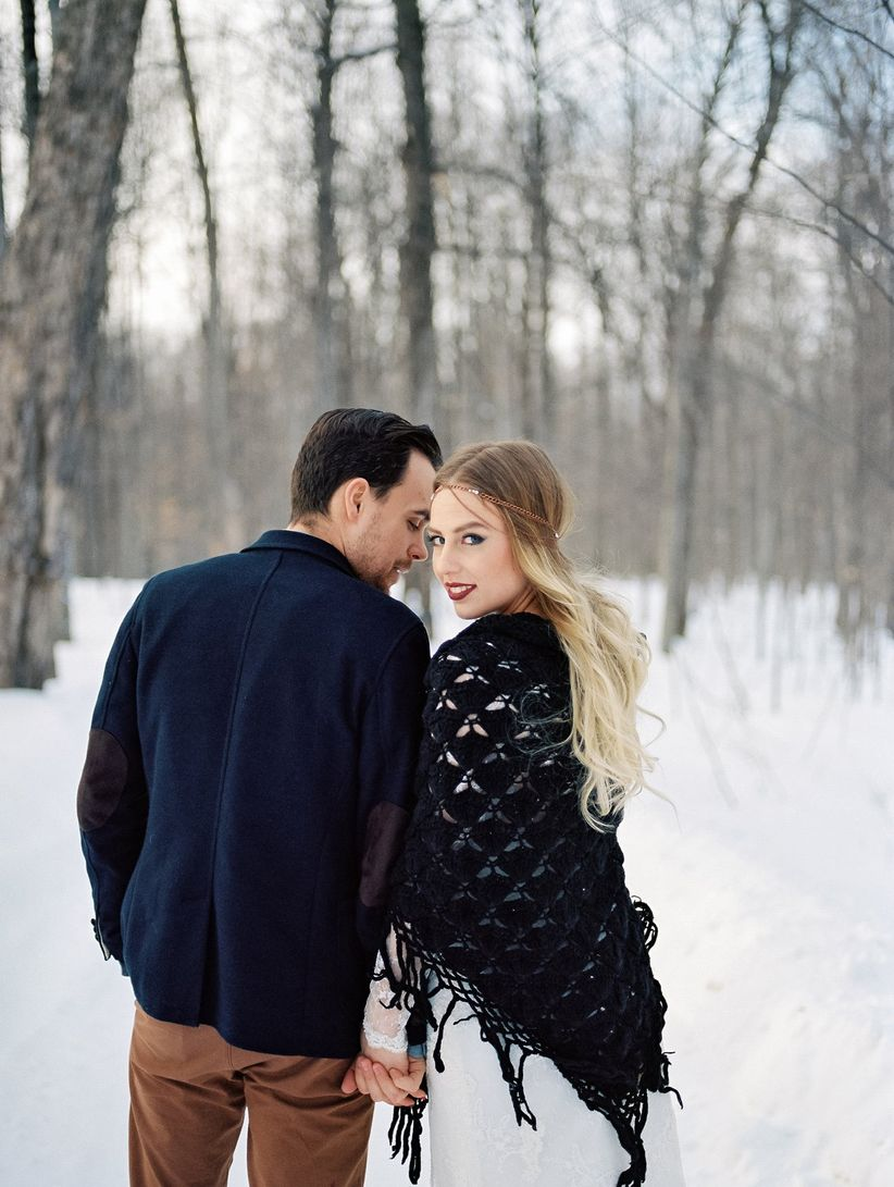 couple portrait bride and groom's backs facing camera outdoor in snow bohemian attire