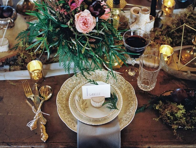 rustic table with vintage gold flecked places gold silverware and outdoorsy centerpiece