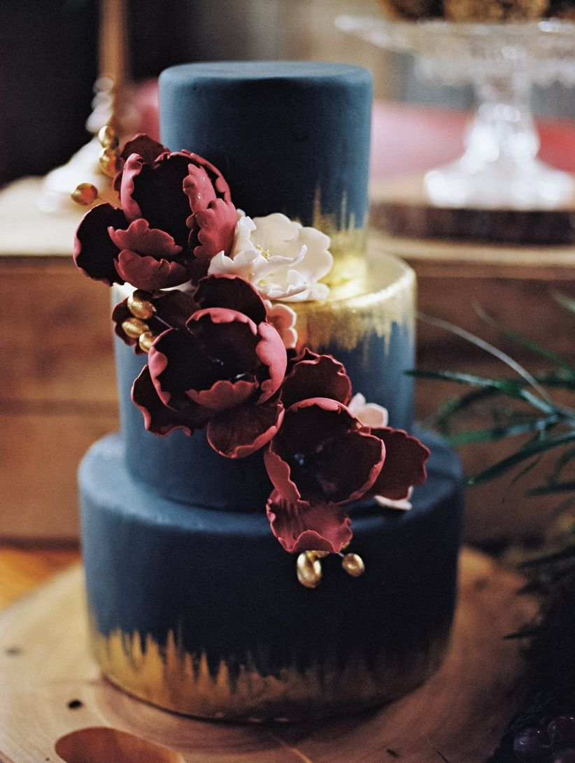 three-tiered navy hued fondant cake with gold accents and cascading florals