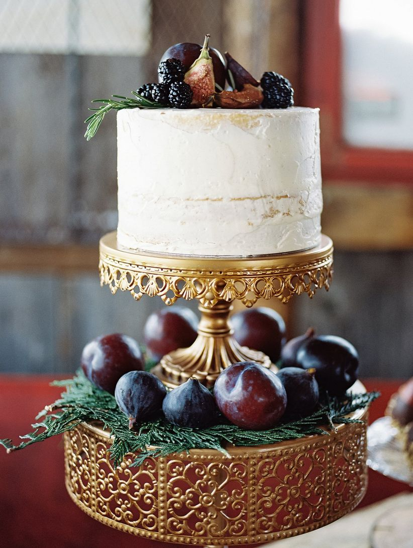 single tiered semi naked cake on two tiered vintage cake stand with fruit