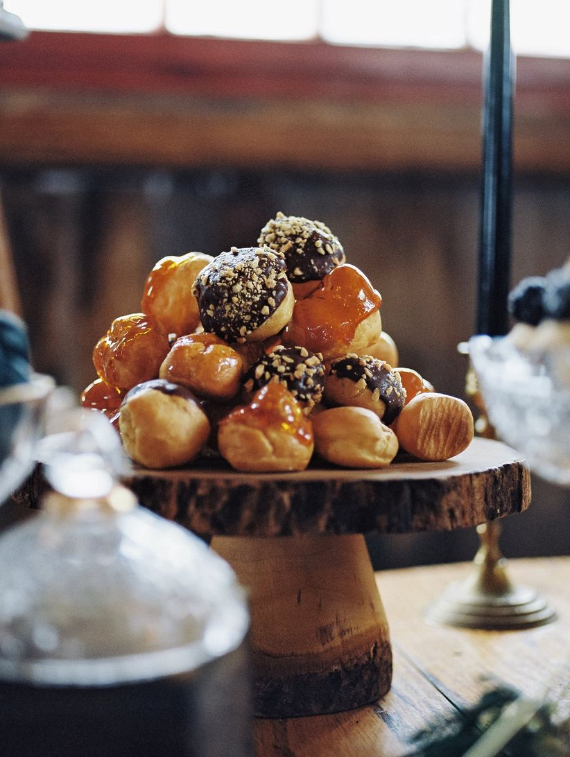 chocolate and caramel covered pastries displayed on wooden cake stand