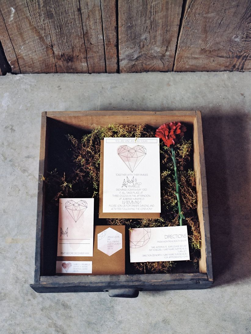 Geometric inspired invitation suite with pink water color displayed in moss filled box