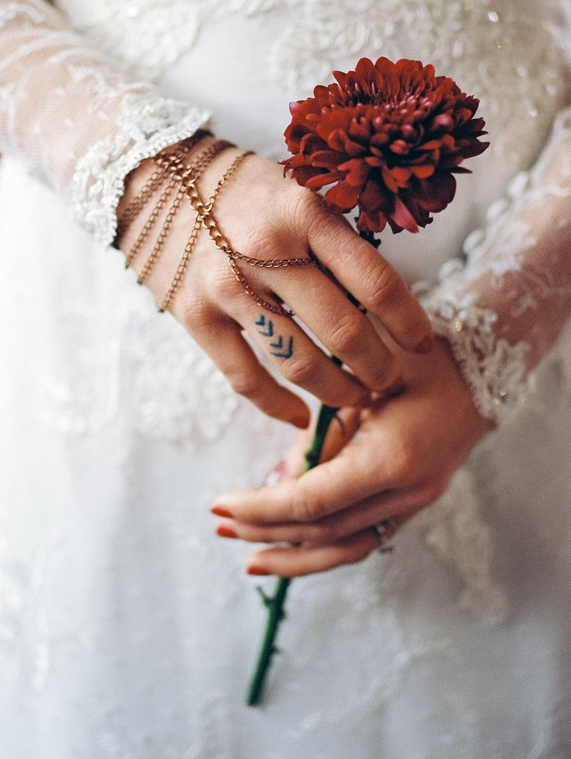 bride with red nails and delicate finger tattoo holding chrysanthemum