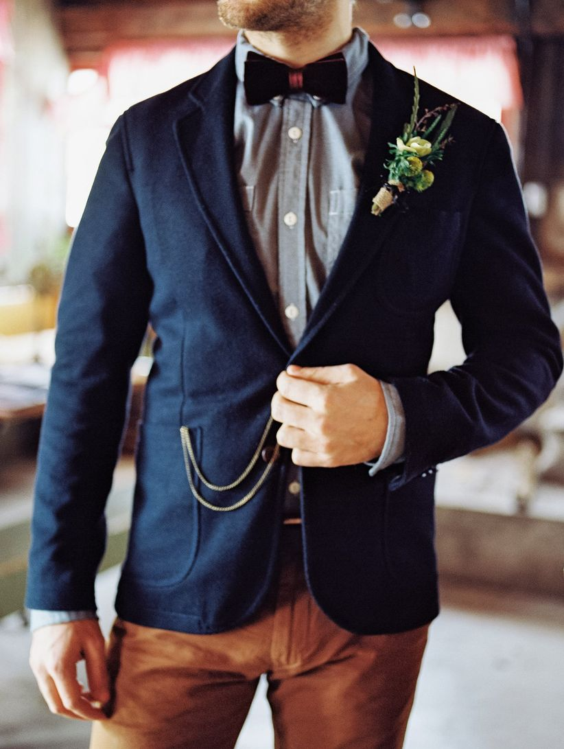 close up casual groom attire navy jacket chambray button down velvet bow tie brown slacks