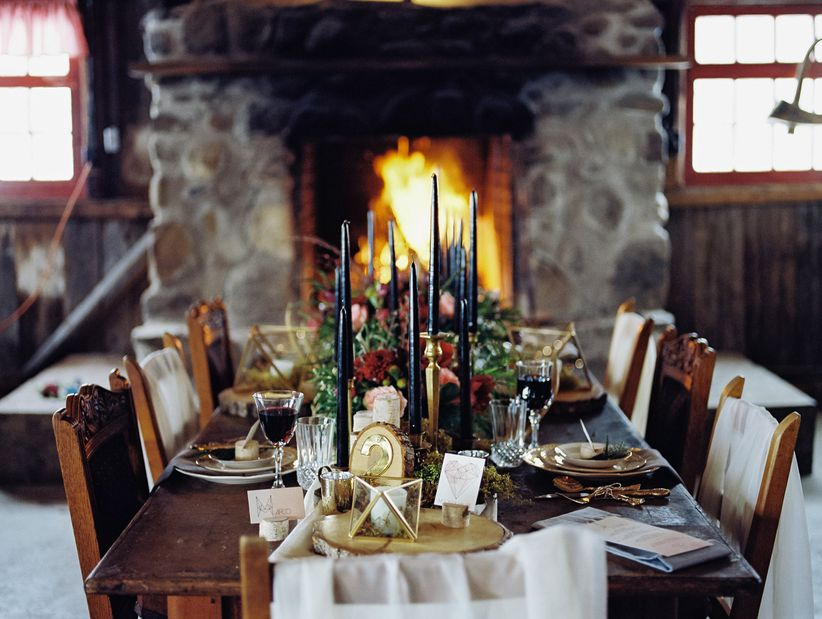 rustic tablescape navy hued candles floral centerpiece wood slices in front of stone fireplace