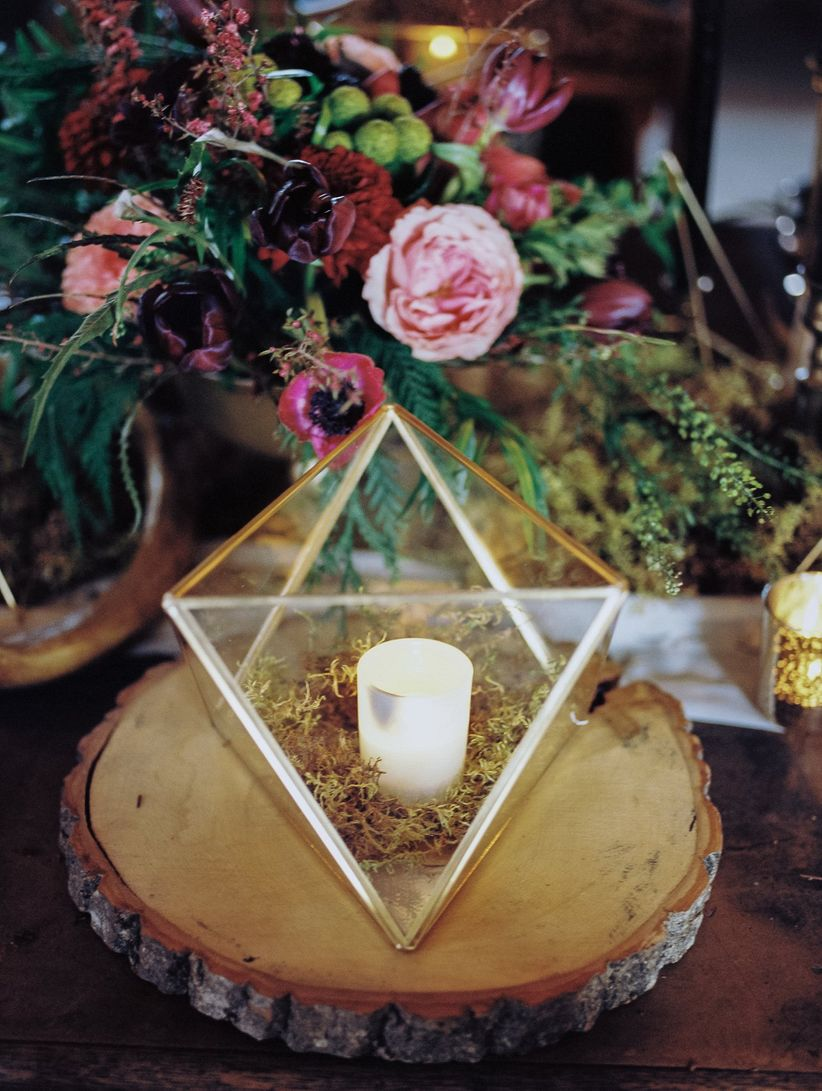 Geometric prism candle holder on wooden slice next to floral centerpiece
