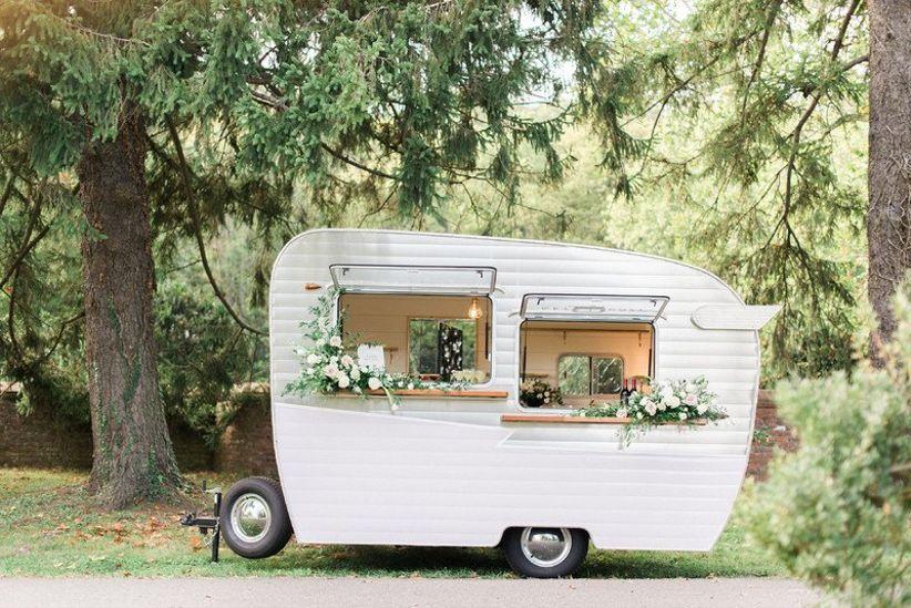 mid century modern wedding idea —vintage camping trailer serves drinks as mobile bar