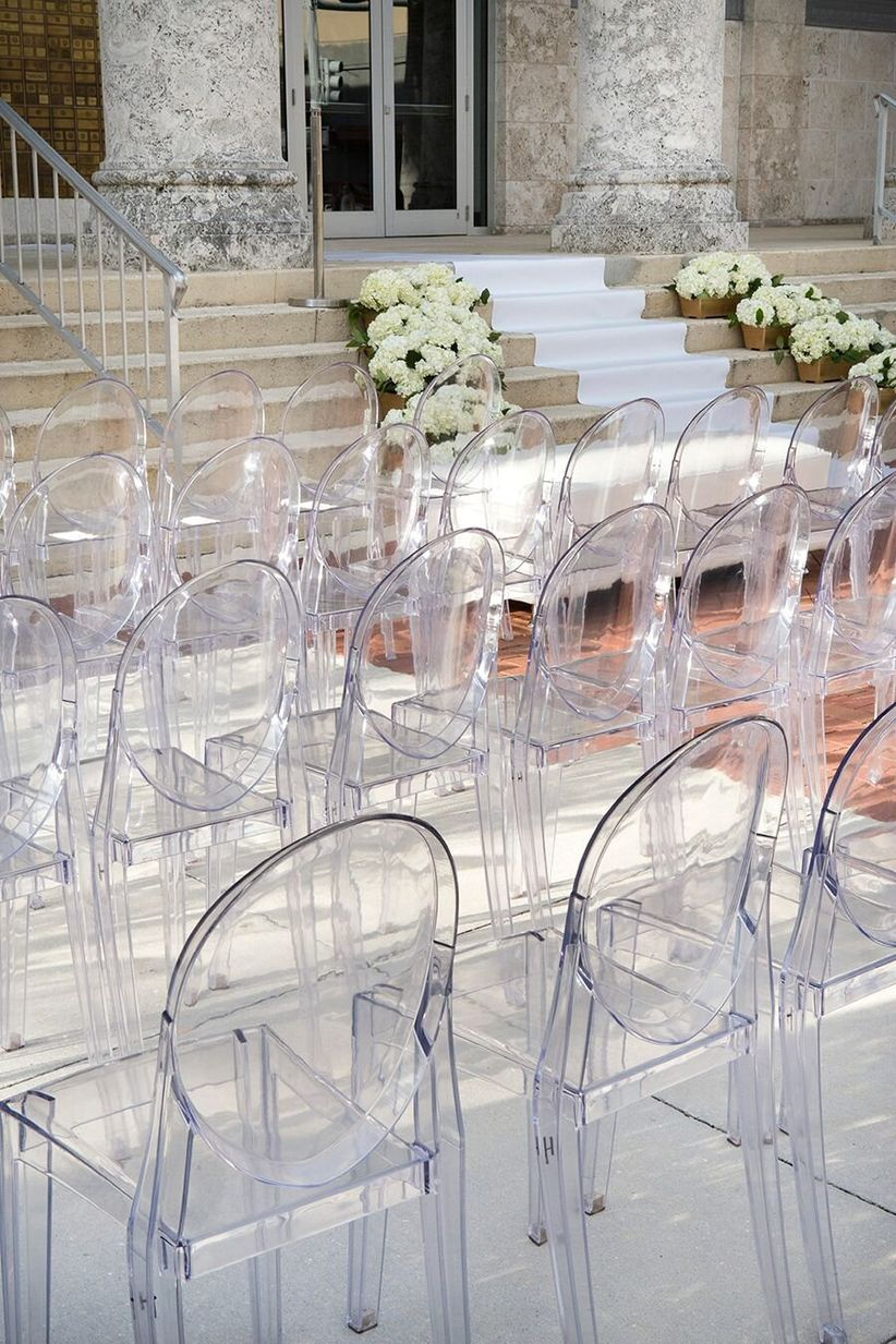 ghost chairs at outdoor ceremony