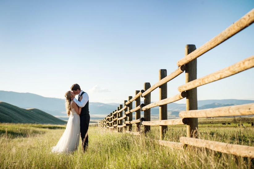 bride and groom pose for romantic kiss at rustic wedding venue in Montana with mountain views