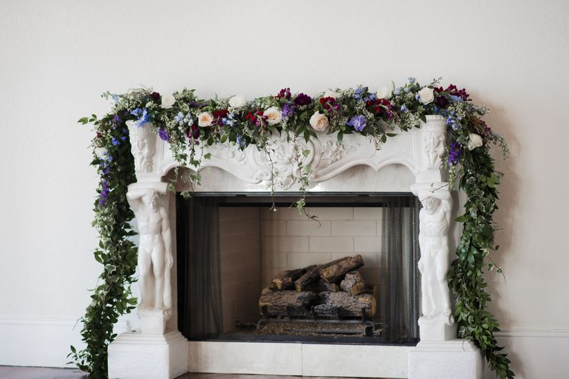 white fireplace mantel at historic wedding venue decorated with greenery and flower garland