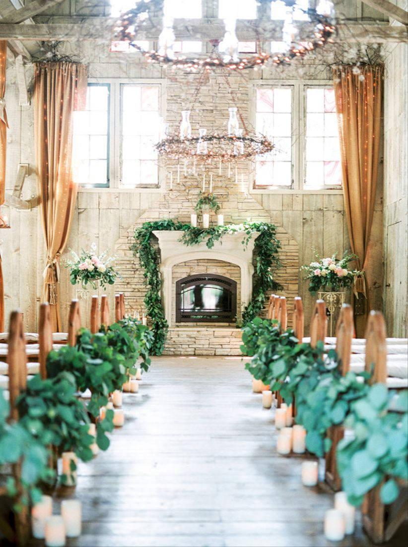 stone fireplace decorated with greenery at indoor ceremony wedding venue, candles and greenery line the long aisle