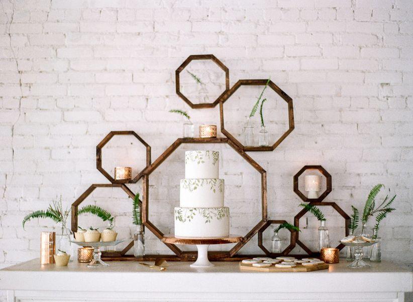 modern bohemian wedding dessert display with geometric wooden octagon backdrop and greenery
