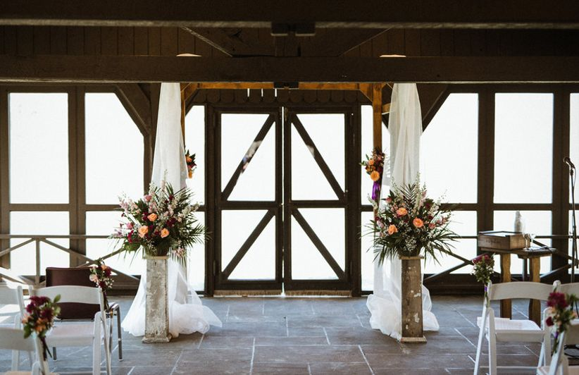 indoor wedding ceremony altar with white draping and flowers