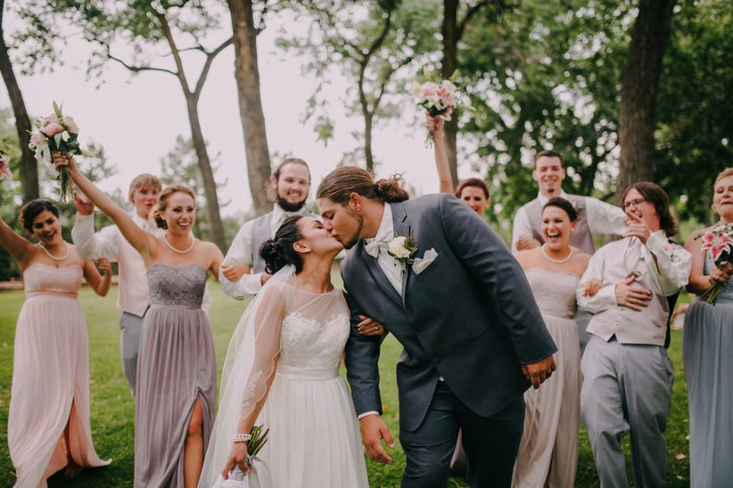 couple kissing and walking with wedding party