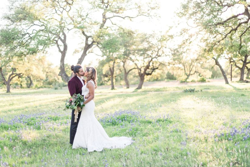bride and groom pose for romantic wedding photo in field surrounded by trees and wildflowers