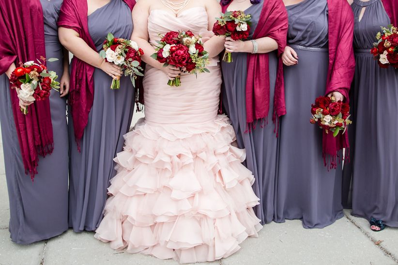 winter bride with blush wedding dress standing next to bridesmaids