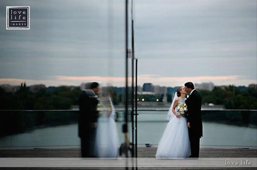bride and groom kiss in front of House of Sweden in Washington, DC