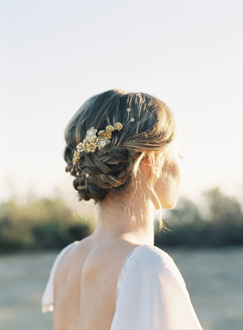 romantic loose braid wedding updo with gold barrette