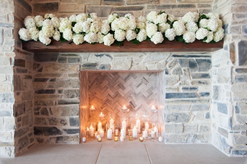 beautiful stone and wood fireplace mantel decorated with clusters of white hydrangeas and candles
