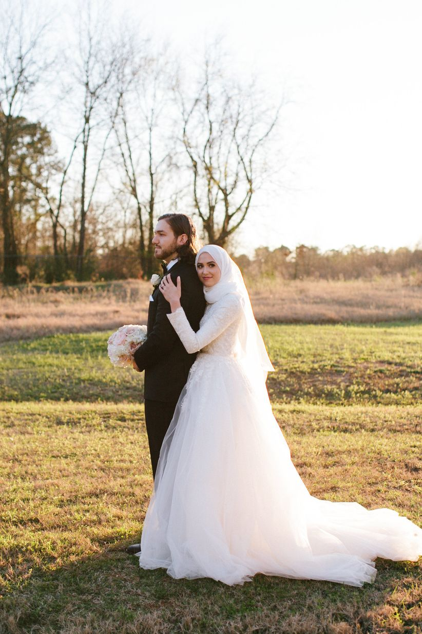 After their Muslim wedding, a bride and groom pose in their wedding attire in an open field.